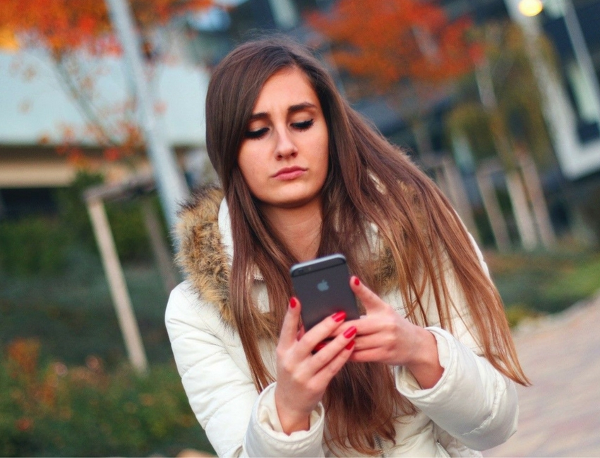 Teen girl on her phone on campus in winter