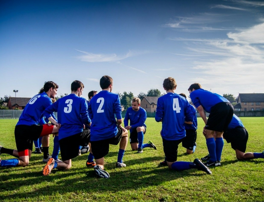 Teen boy's soccer team kneeling in a huddle